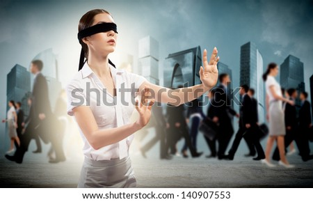 young blindfolded woman. seeking a way out in a crowd - stock photo