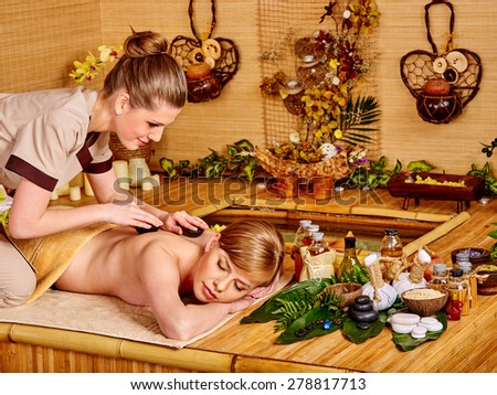 Young blond beautiful woman getting massage in bamboo spa. - stock photo