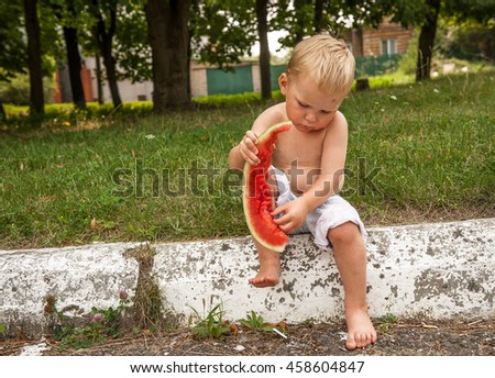 Young blond boy has healthy eating habits. eating watermelon, healthy fruit snack, adorable toddler child with curly hair playing in a sunny garden on a hot summer day. portrait - stock photo