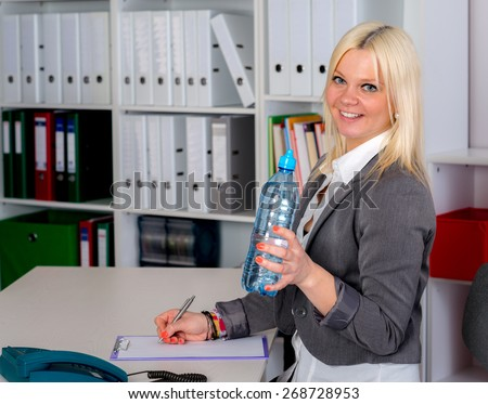 young blond businesswoman is drinking water in the office - stock photo