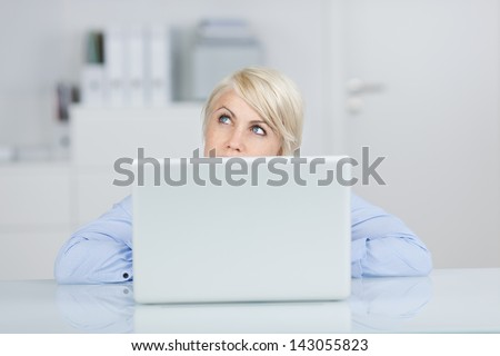 Young blond businesswoman looking up thoughtfully in front of a laptop at office desk - stock photo