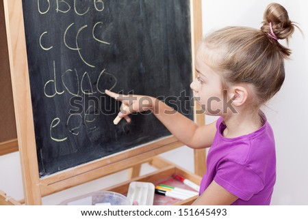 Young blond caucasian girl learning to write letters on blackboard - stock photo