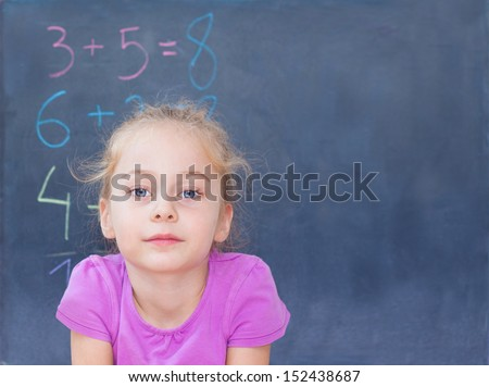 Young blond five years old caucasian girl in front of blackboard at school - mathematics lesson - stock photo