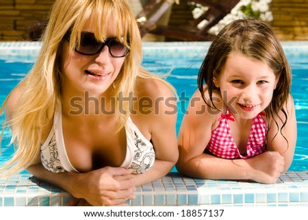 Young blond girl and her sister enjoying the sun in and around the swimming pool - stock photo