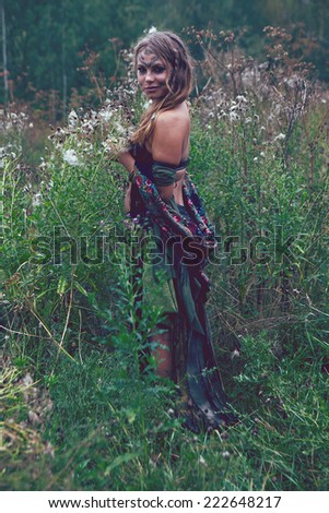Young blond girl dancing in the  field with large grass - stock photo