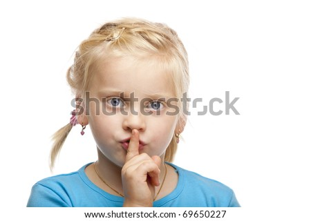 Young blond girl holds finger on mouth. Isolated on white background. - stock photo