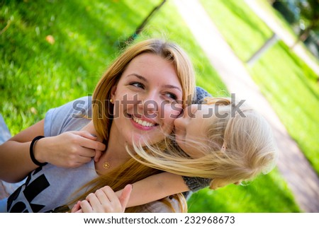 young blond girl hugging and kissing her smiling mom - stock photo