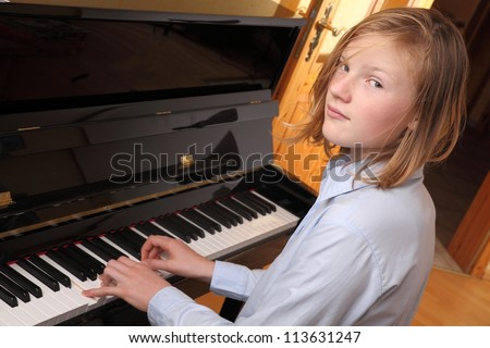 Young blond girl plays piano - stock photo