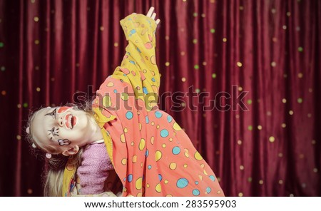 Young Blond Girl Wearing Clown Make Up and Polka Dot Costume Shielding Eyes from Bright Stage Lights in front of Red Curtain - stock photo