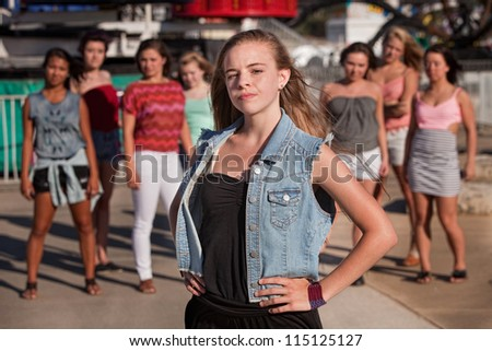 Young blond girl with a confident attitude in front of friends - stock photo
