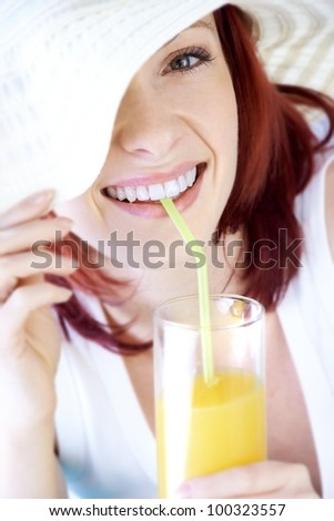 young blond girl with hat and fruit juice - stock photo