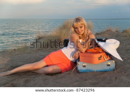 Young blond girl with her luggage sitting nicely on the sand on the beach. She came to the warm country to relax. Light of the sun at sunset. - stock photo
