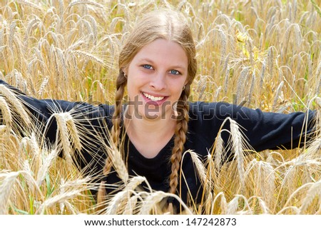 Young, blond girl with pigtails in a wheat field - stock photo