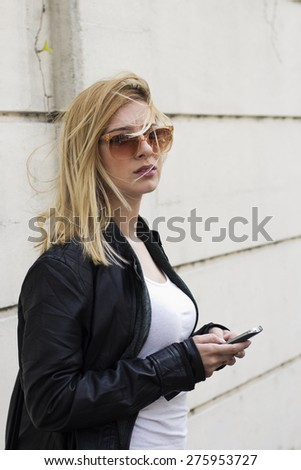 Young blond haired woman with sunglasses and wind in her hair standing and holding a smart phone . - stock photo