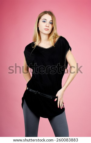 Young blond lady in black dress posing on pink background - stock photo