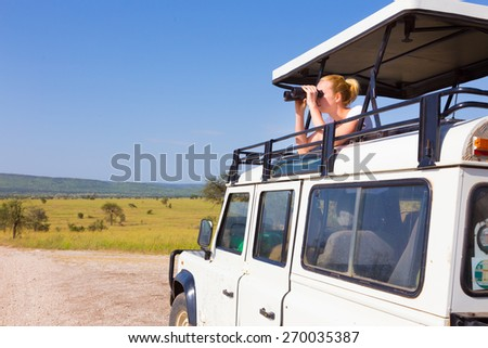Young blond lady on safari standing in open roof jeep observing wild animals through binoculars. - stock photo
