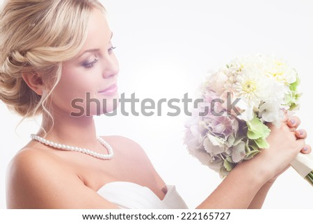 Young blond lady wearing wedding dress and holding a bridal bouquet - stock photo