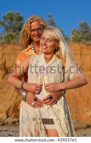Young blond man and blond woman are posing and are looking at camera outdoors - stock photo
