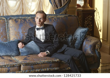Young blond man in suit and bow tie sitting on blue sofa in old luxury interior - stock photo