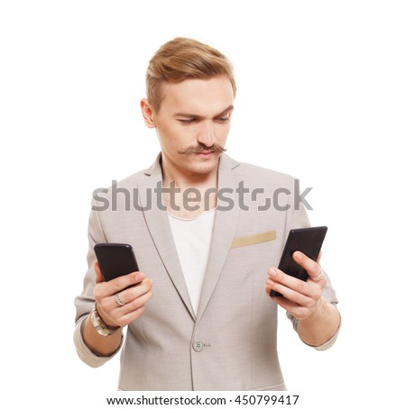 Young blond man with mustache choose between two cell phones. Guy looks at mobile, selecting which to buy. Comparing smartphones in hands. Male portrait isolated at white background - stock photo
