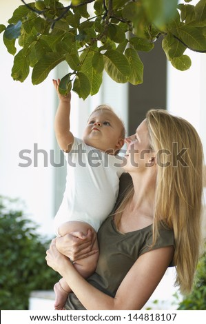 Young blond mother carrying child under tree - stock photo