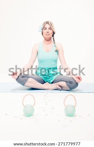 Young Blond Peaceful Woman Meditating in Seated Yoga Lotus Position on Mat with Two Candle Holder Pots and Trail of Daisy Flowers - stock photo