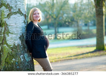 young blond pregnant woman alone  the park - stock photo