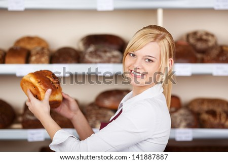 young blond saleswoman taking bread from shelf in bakery - stock photo