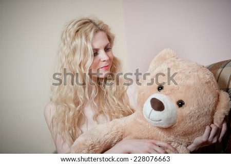 Young blond sensual woman sitting on sofa relaxing with a huge teddy bear. Beautiful girl with comfortable clothes relaxing on the couch with a toy. Attractive blonde in cozy scenery indoor - stock photo