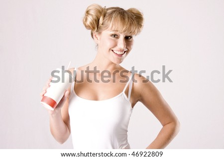 young blond sportswoman in white sportswear takes a drink - stock photo