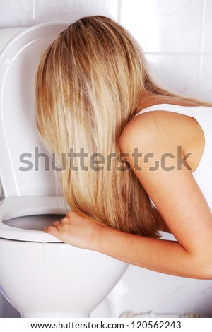Young blond teen woman vomiting in toilet - stock photo