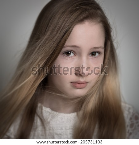 Young blond teenage girl with long hair with a sad face, crying isolated against a grey background - stock photo