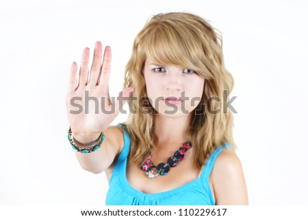 Young blond teenager girl with sad or angry face raising her hand to say NO or STOP, strong concept against drugs, violence, abuse or others: focus on hand in forefront. - stock photo