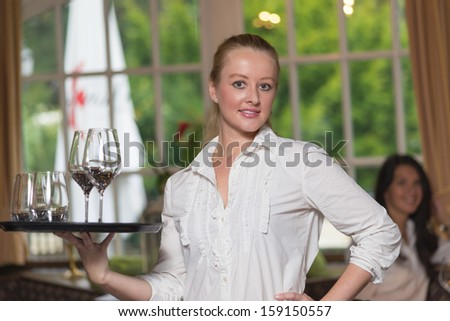 Young blond waitress in restaurant holding a tray full of glasses - stock photo