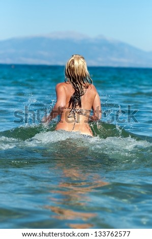 Young blond woman at the ocean - stock photo