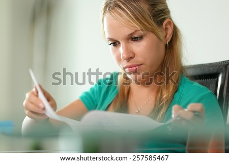 Young blond woman, college student, studying with motivated and concentrated expression - stock photo