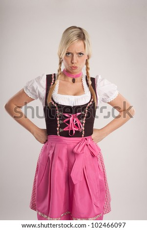young blond woman dressed with dirndl for oktoberfest is disappointed/young blond angry woman with dirndl costume/woman with dirndl is angry - stock photo