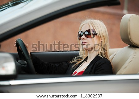 Young blond woman driving a convertible car - stock photo