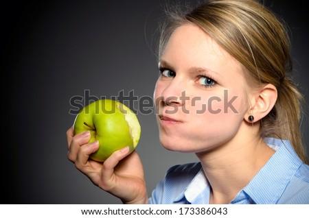 young blond woman eats joyfully a green apple - stock photo