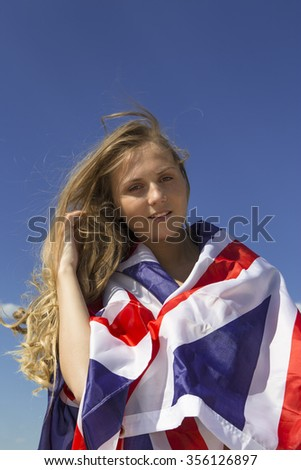 Young blond woman holding British national flag in arms - stock photo