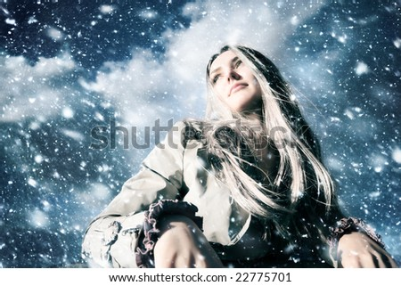 Young blond woman in a blizzard. Wide angle view. - stock photo