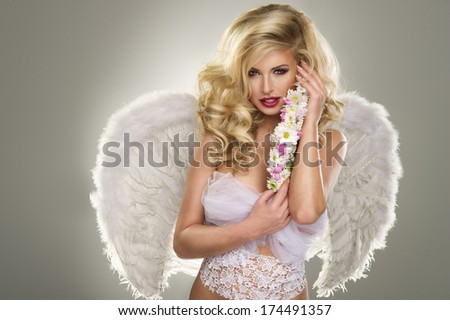 Young blond woman in angel costume with flower - stock photo