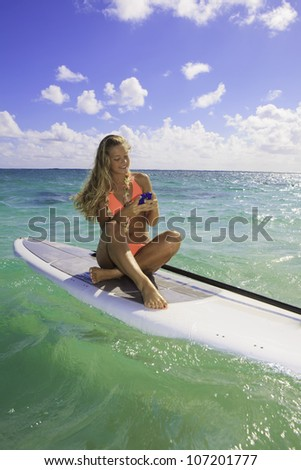 young blond woman in bikini on paddle board texting on her cell phone - stock photo