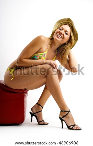 Young blond woman in bikini sitting on red pouffe - stock photo