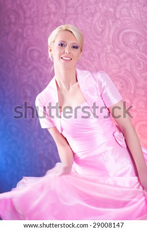 Young blond woman in pink dress dancing. Soft pink and blue background. - stock photo