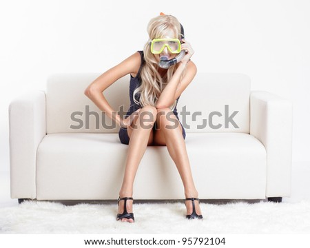 young blond woman in scuba mask on couch with white furs on floor - stock photo
