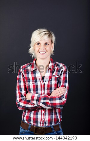Young blond woman in shirt standing with arms crossed against black background - stock photo