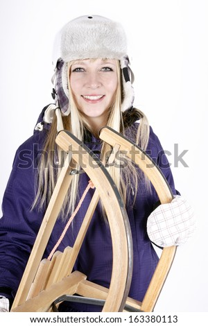 Young blond woman in skiing suit with helmet and sleigh - stock photo