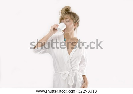 young blond woman in white bathrobe is drinking a cup of tea - stock photo