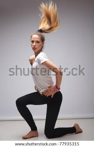 young blond woman in white t-shirt dancing, studio shot, full body shot - stock photo